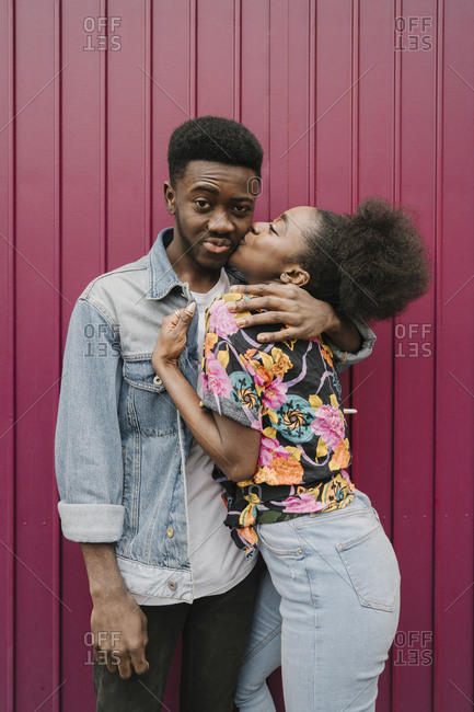 Portrait of young man kissed by his girlfriend