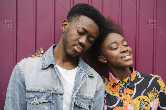 Portrait of happy young couple head to head with eyes closed