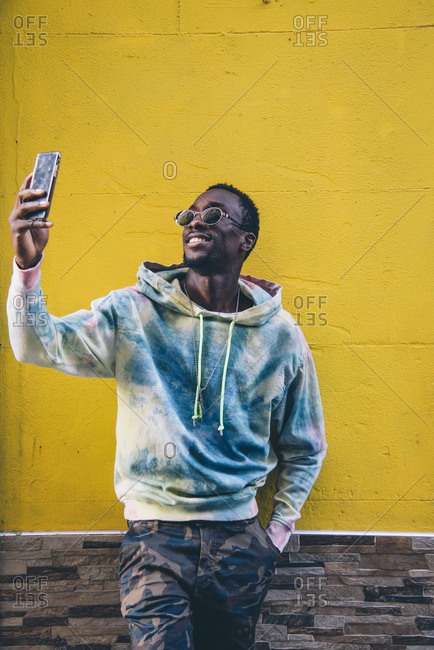 Portrait of smiling young man taking selfie with smartphone in front of yellow wall