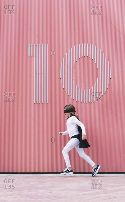Girl in superhero costume running along a wall