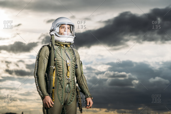 Man posing dressed as an astronaut with dramatic clouds in the background
