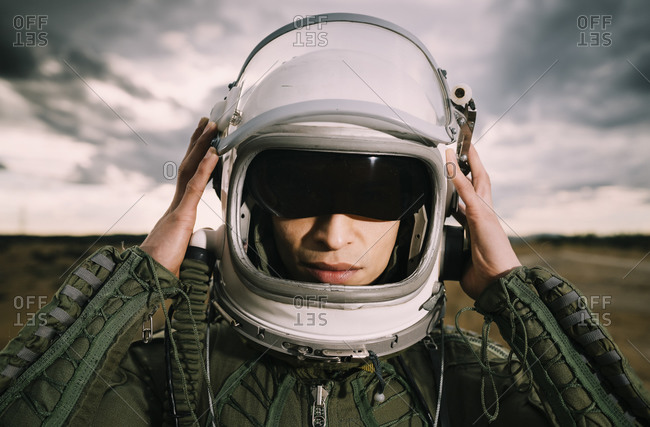 Man with astronaut helmet- dramatic clouds in the background