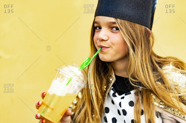 Portrait of content girl drinking soft drink