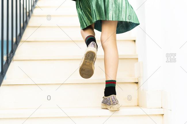 Girl wearing green skirt running upstairs