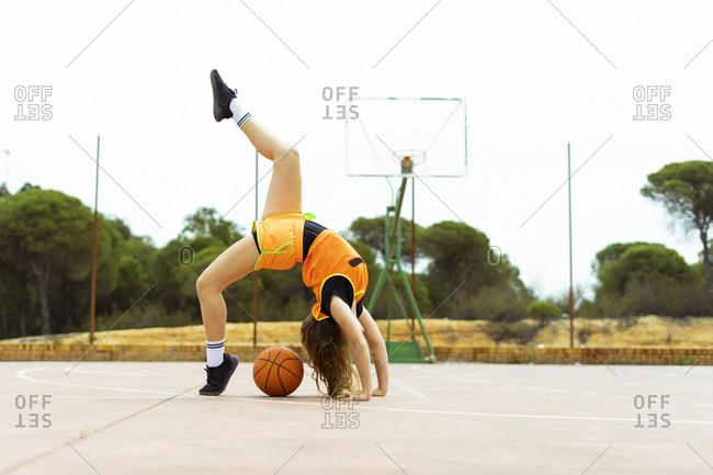 Teenage girl doing acrobatics on basketball ground
