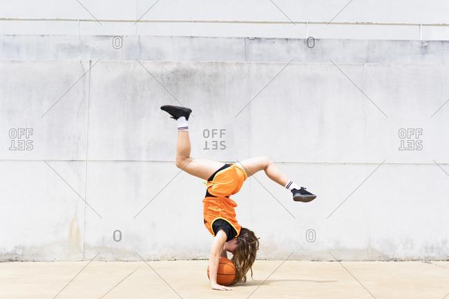 Teenage girl doing acrobatics with basketball outdoors
