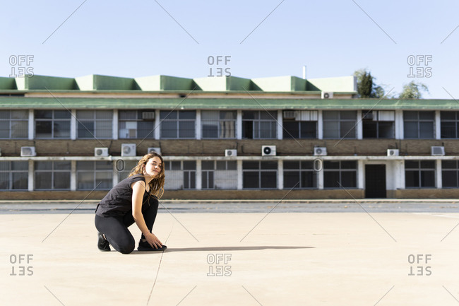 Portrait of teenage girl crouching outdoors