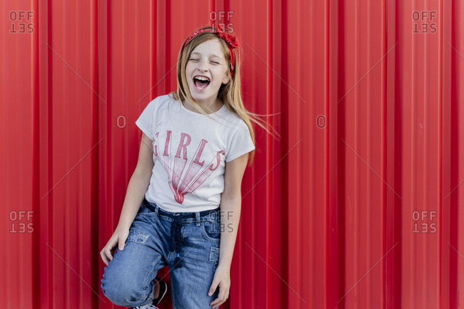 Girl screaming in front of red wall
