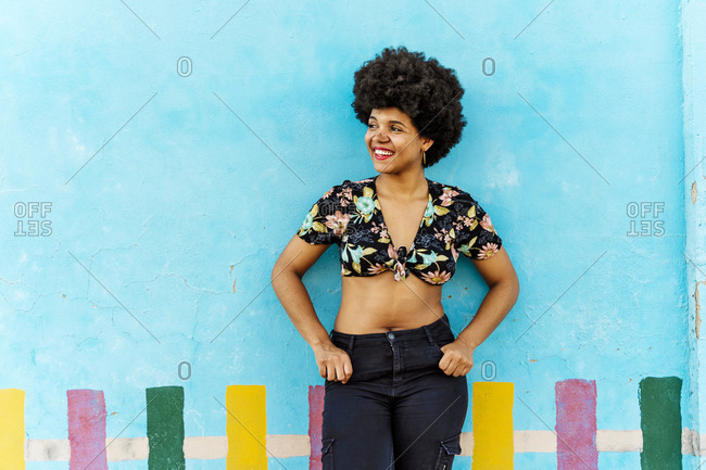 Smiling Afro-American woman in front of a blue wall looking sideways