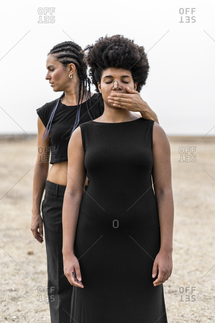 Woman's hand covering mouth of another woman