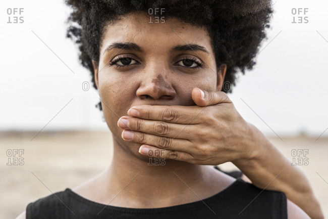 Woman's hand covering mouth of another woman- close-up