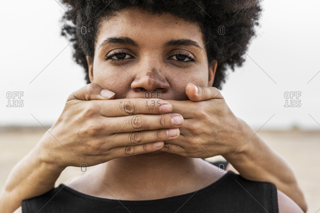 Woman's hands covering mouth of another woman- close-up
