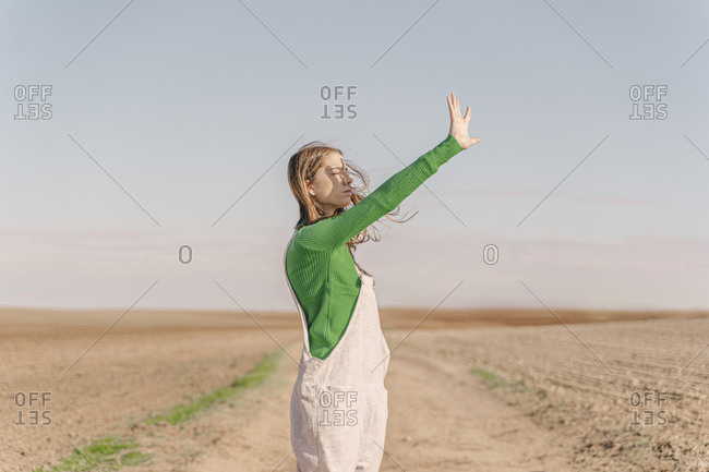 Young woman standing on dry field- shielding eyes
