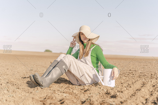 Young woman with watering can sitting on dry field