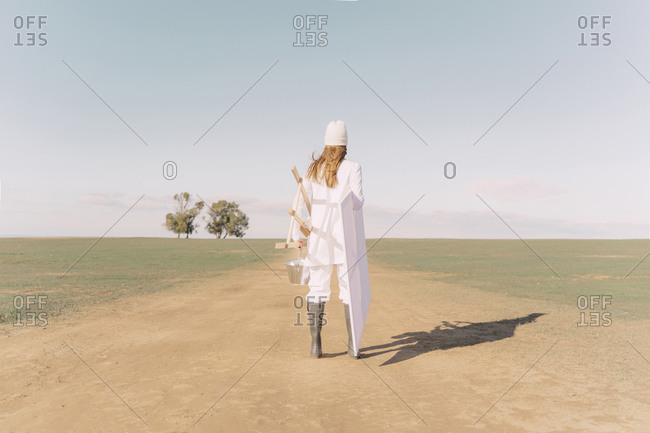 Young woman carrying easel and empty canvas on dry field