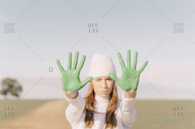 Young woman showing green painted palms