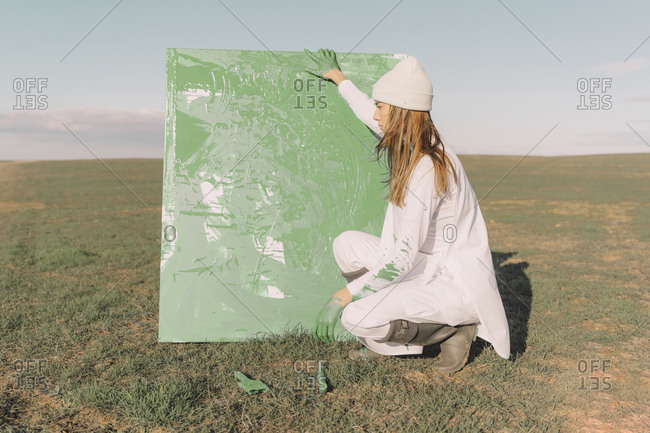 Young woman holding green painting- crouching on dry field
