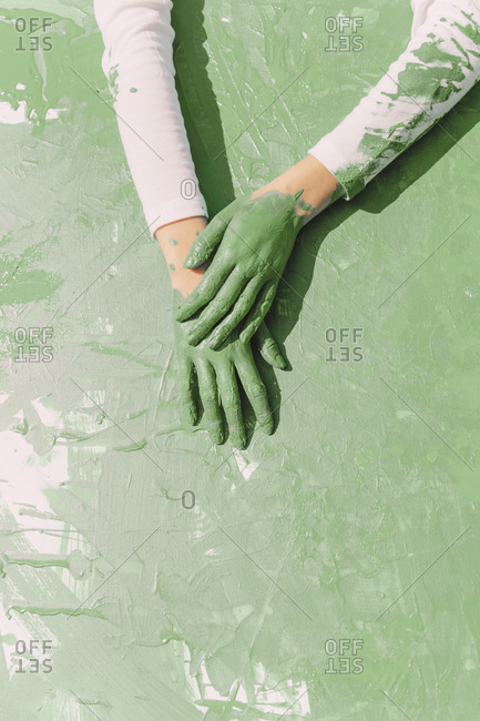 Green hands of young woman on green painting