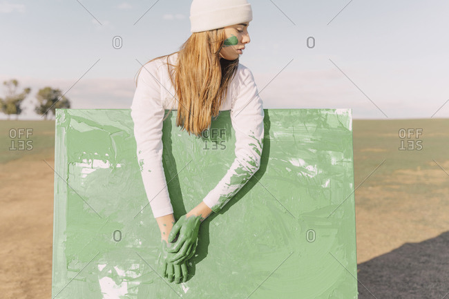 Young woman with green hands on green painting