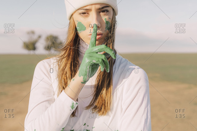 Young woman putting finger of green hand on her mouth