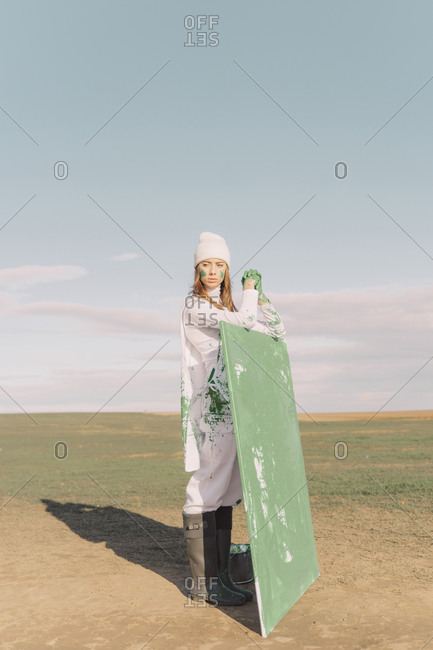 Young woman holding green painting on dry field