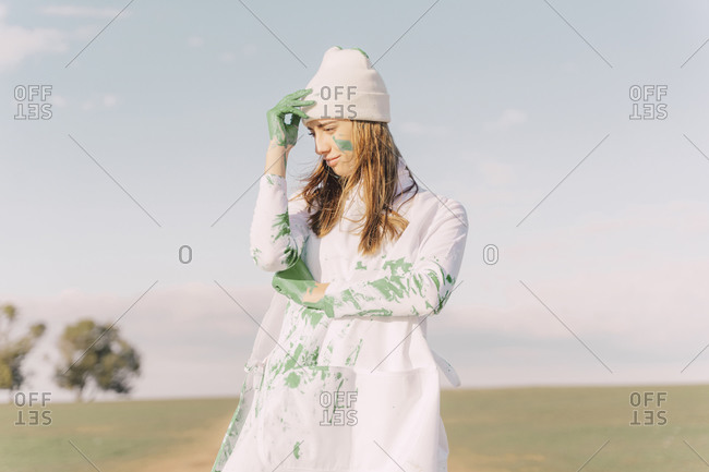 Young woman putting green painted hand on her forehead- thinking