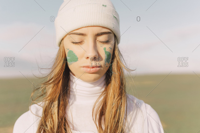 Portrait of young woman with green face paint- eyes closed
