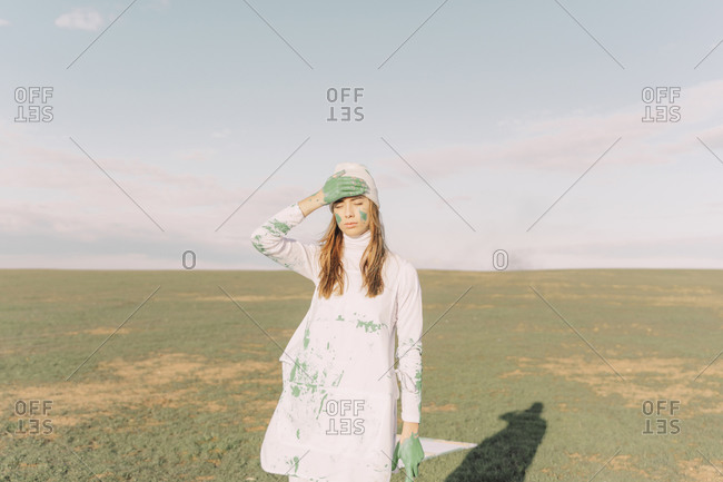 Young woman putting green painted hand on her forehead