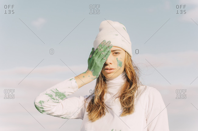 Young woman covering eye with green hand