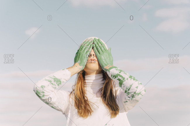 Young woman covering eyes with green hands