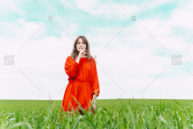 Portrait of woman wearing red dress standing in a field with finger on mouth