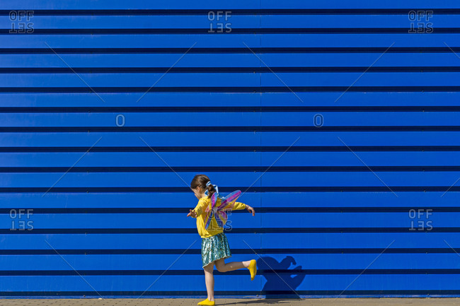 Little girl with colorful butterfly wings balancing on one leg in front of blue background