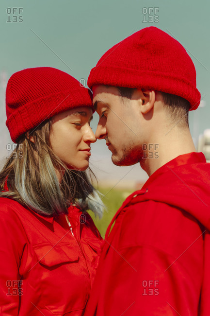 Young couple dressed in red  standing head to head with eyes closed