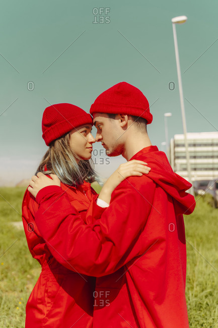 Young couple wearing red overalls and hats standing head to head looking at each other