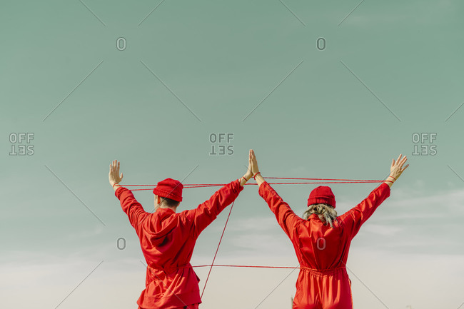 Back view of young couple wearing red overalls and hats performing with red string outdoors