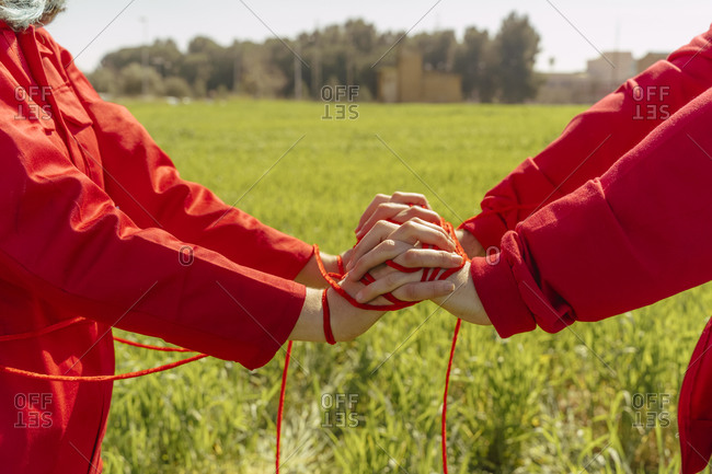 Crop view of young couple dressed in red performing on a field with red string