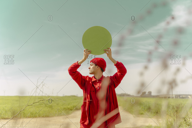 Young man dressed in red holding green circle