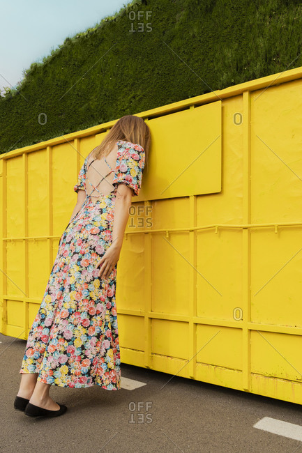 Desperate woman leaning head on yellow container in the street