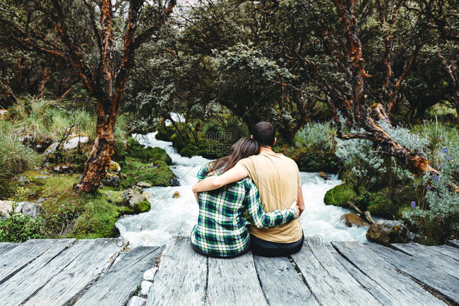 Peru- couple sitting arm in arm on a wooden bridge enjoying nature