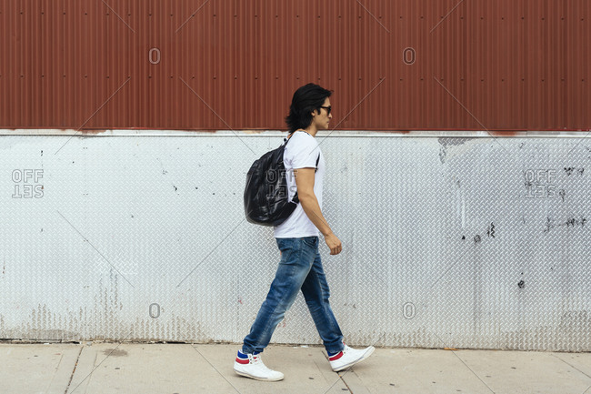 Man with a backpack walking on the sidewalk