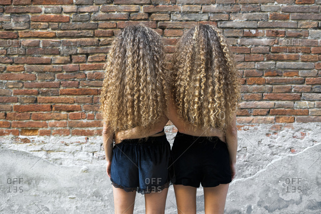Back view of twin sisters with ringlets standing arm in arm side by side