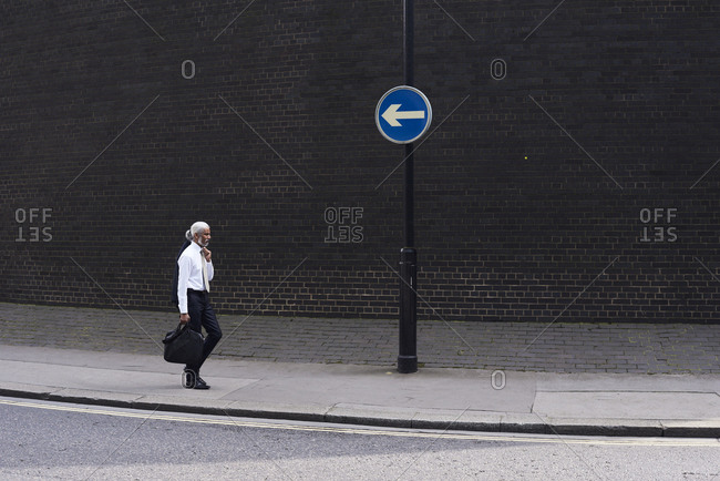 Elegant senior businessman with luggage walking on pavement in the opposite direction