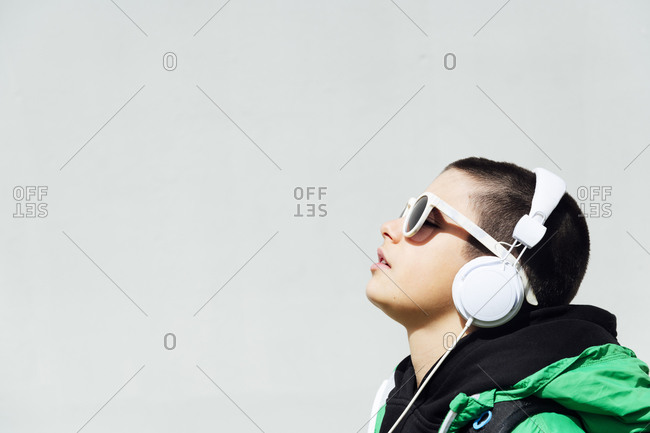 Boy wearing sunglasses listening music with headphones