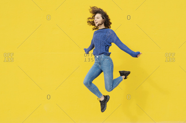 Young woman jumping in the air in front of yellow background