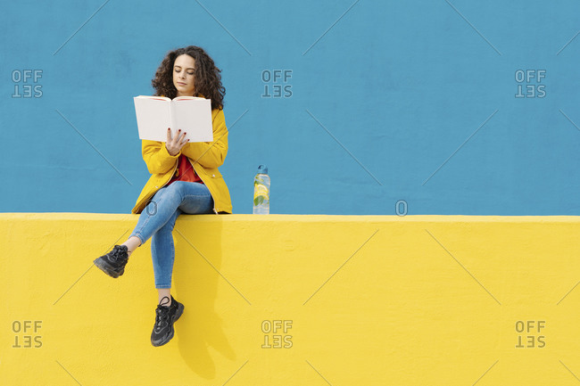 Young woman sitting on yellow wall reading a book