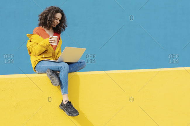 Happy young woman with coffee to go sitting on yellow wall using laptop