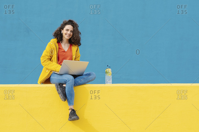 Portrait of smiling young woman with earphones and laptop sitting on yellow wall