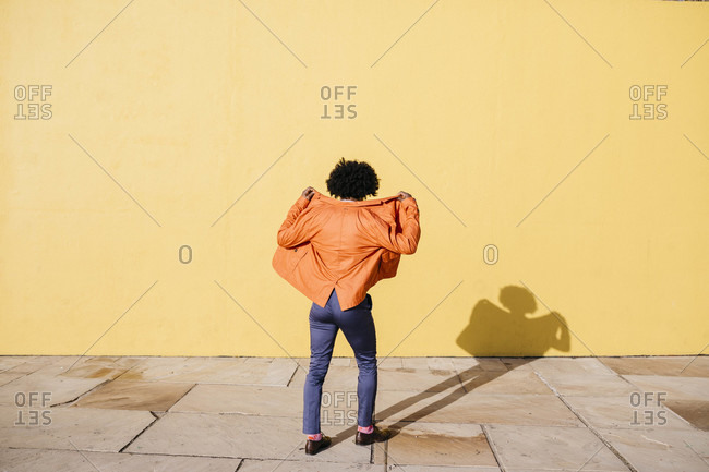 Back view of man wearing orange suit coat in front of yellow wall