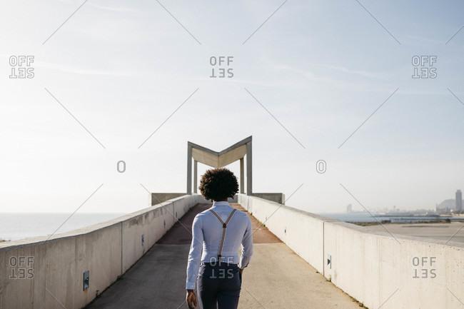Spain- Barcelona- back view of man walking on a bridge