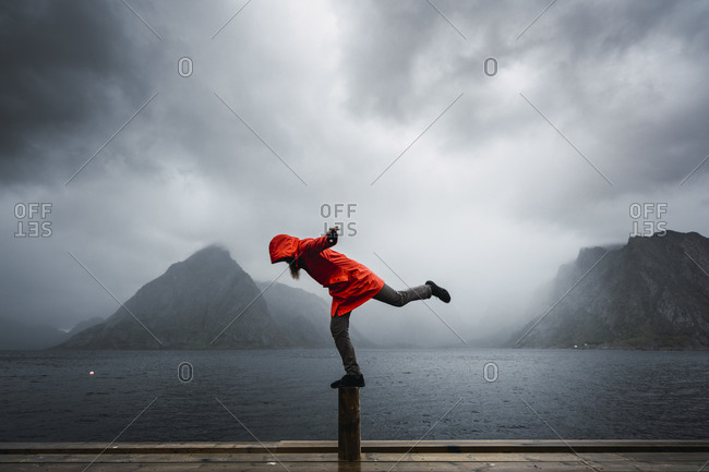 Norway- Lofoten- man balancing on a pole at the coast